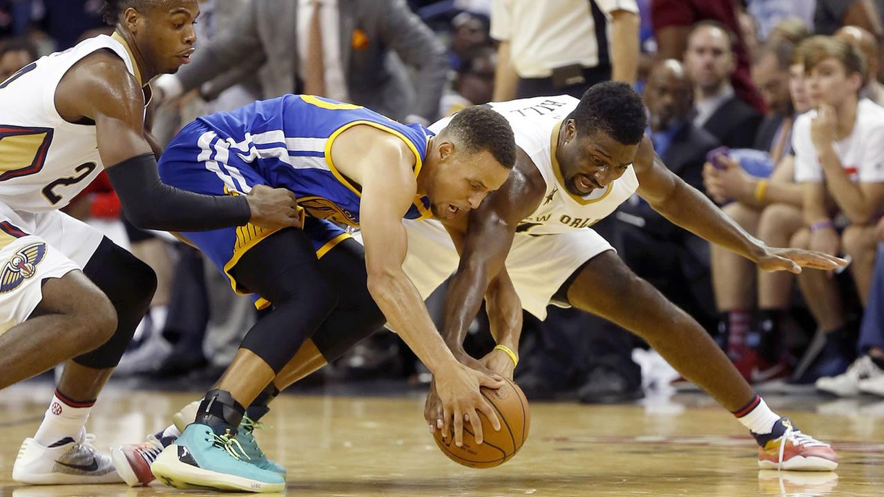 Golden State Warriors guard Stephen Curry, center, attempts to recover a lose ball against New Orleans Pelicans guard Buddy Hield, left, during in in New Orleans Oct, 28, 2016.