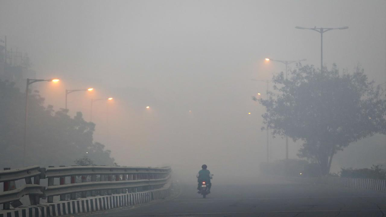 A man rides a scooter on a road enveloped by smoke and smog, on the morning following Diwali festival in New Delhi, India, Monday, Oct. 31, 2016.
