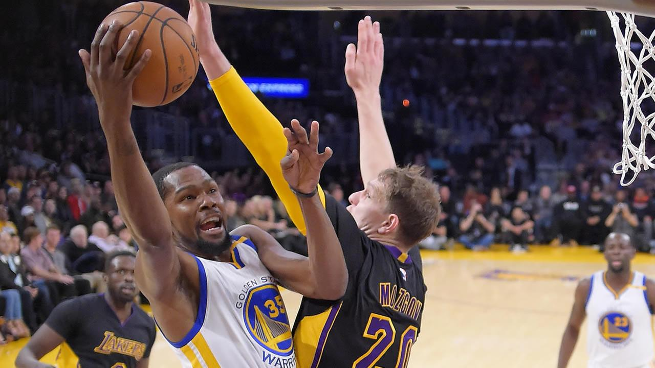 Warriors Kevin Durant shoots as Lakers  Timofey Mozgov  defends during the first half of an NBA basketball game, Friday, Nov. 25, 2016, in Los Angeles. (AP Photo/Mark J. Terrill)