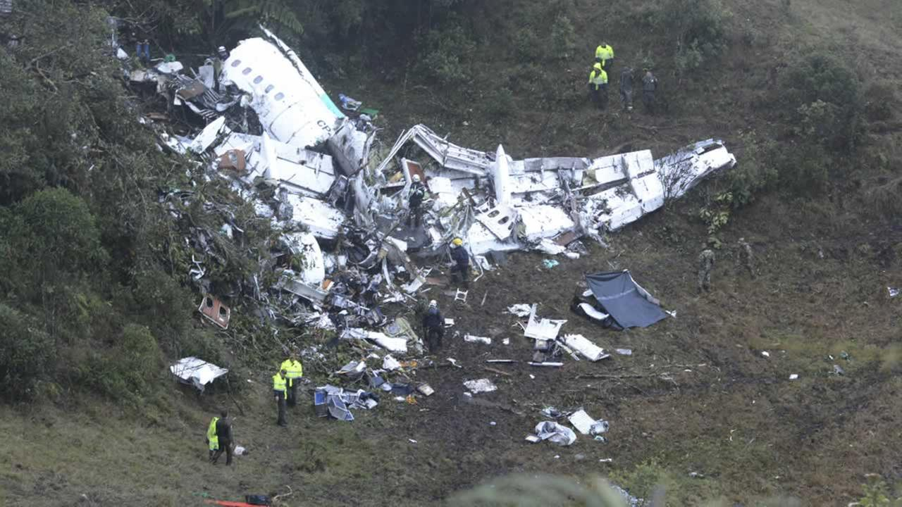 Police officers and rescue workers search for survivors around the wreckage of a chartered airplane that crashed in La Union,  outside Medellin, Colombia.