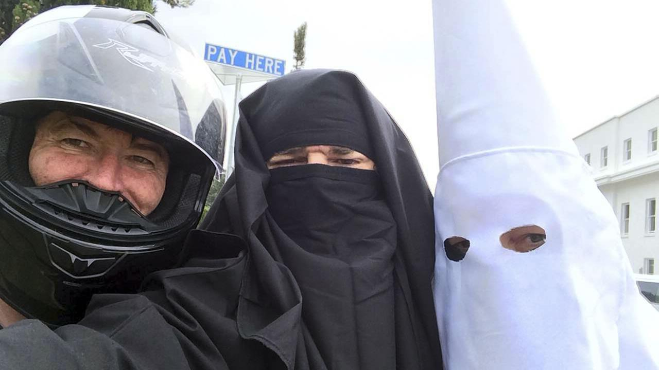 Three men wearing a Ku Klux Klan hood, a niqab and a motorcycle helmet pose for a photo outside Australias Parliament House in Canberra, Monday, Oct. 27, 2014.