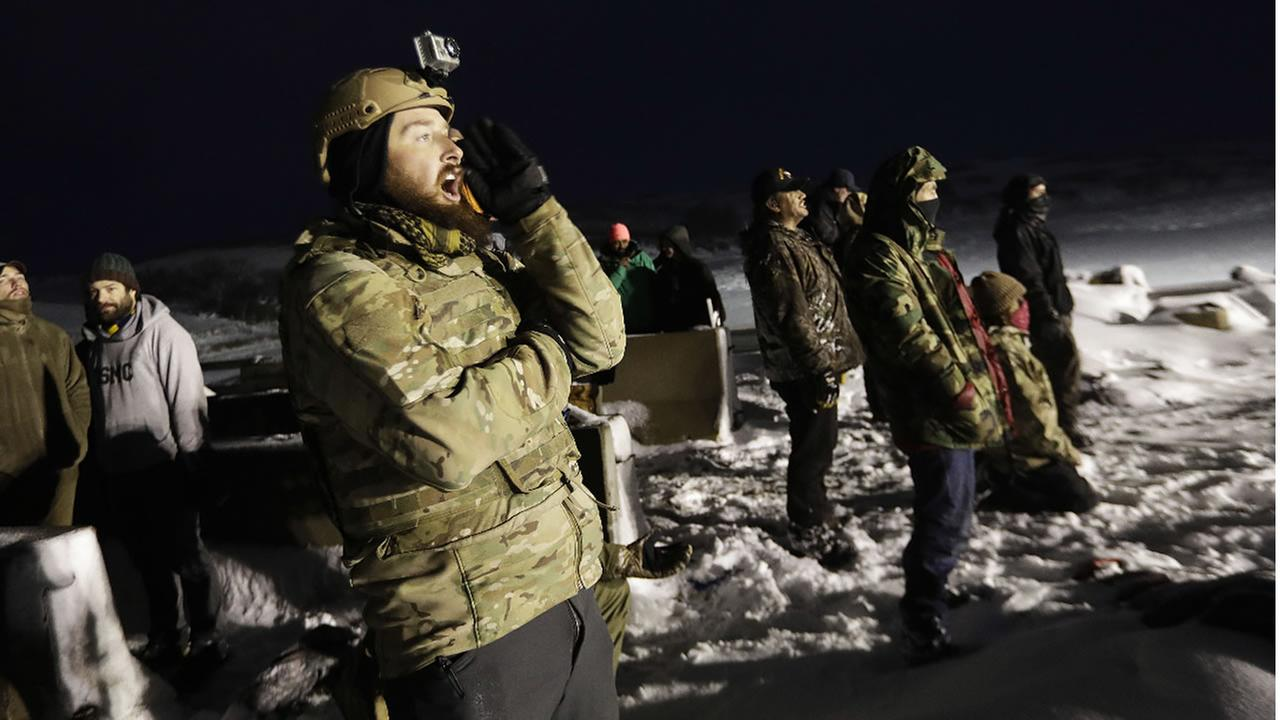 Army veteran Mark Sanderson, of Austin, Texas, protests on a closed bridge across from police protecting the Dakota Access oil pipeline.