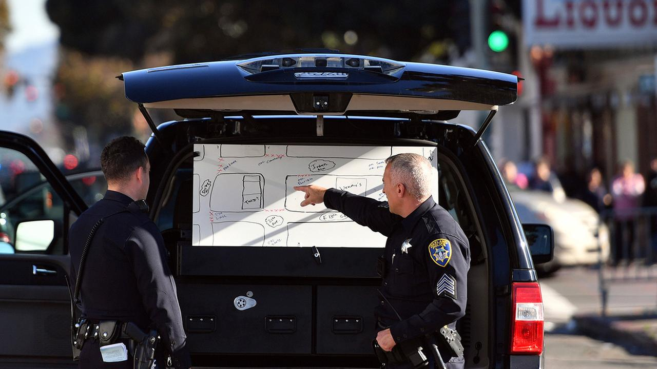 Police officers review a map of the scene of a warehouse rave party in Oakland, Calif., where a fire killed occupants earlier in the morning on Saturday, Dec. 3, 2016.AP Photo/Josh Edelson