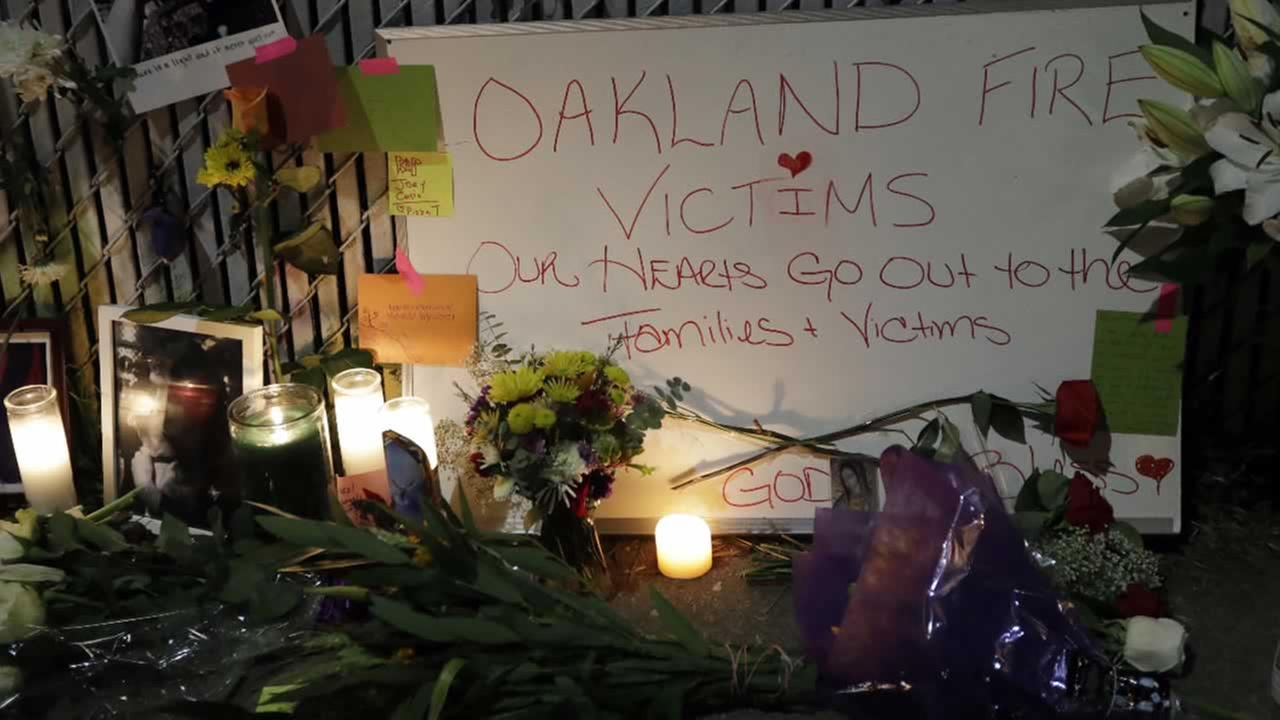 Candles, photos and flowers are placed at a makeshift memorial near the site of a warehouse fire Monday, Dec. 5, 2016, in Oakland, Calif.