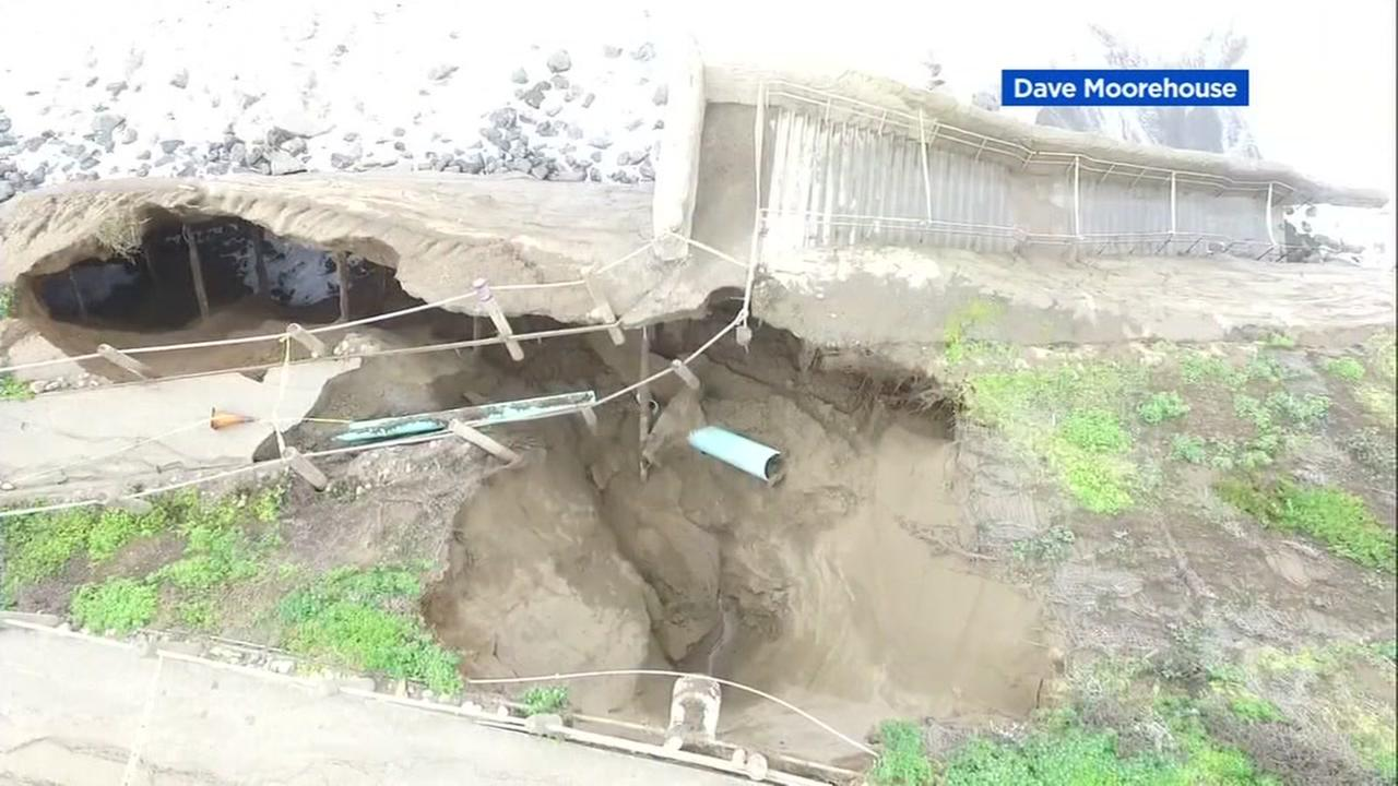 Drone video of a path collapse in Pacifica, Calif. shows a large green pipe now exposed.