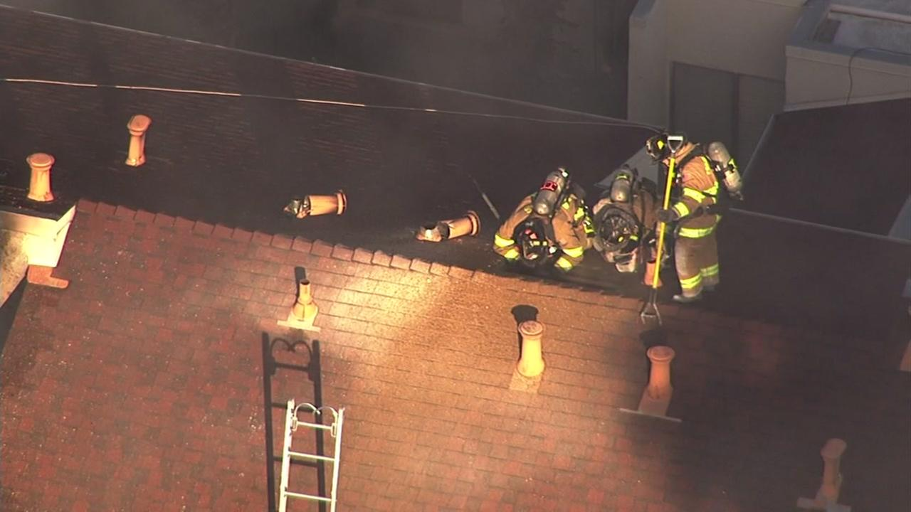 Firefighters stand on the roof of an apartment complex in Concord, Calif. after a two alarm fire broke out on Dec. 19, 2016.