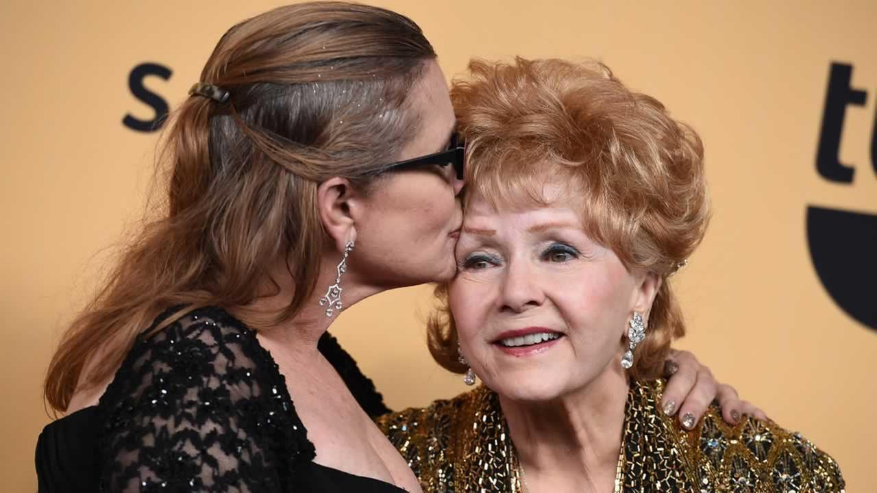 Carrie Fisher, left, and Debbie Reynolds, pose at the 21st annual Screen Actors Guild Awards at the Shrine Auditorium on Sunday, Jan. 25, 2015, in Los Angeles.