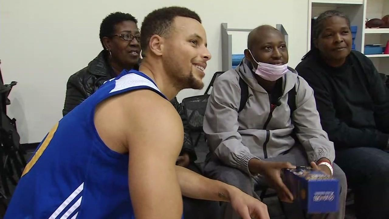 Golden State Warriors point guard Stephen Curry sits with Oakland high school football player Darryl Aikens on Dec. 29, 2016.