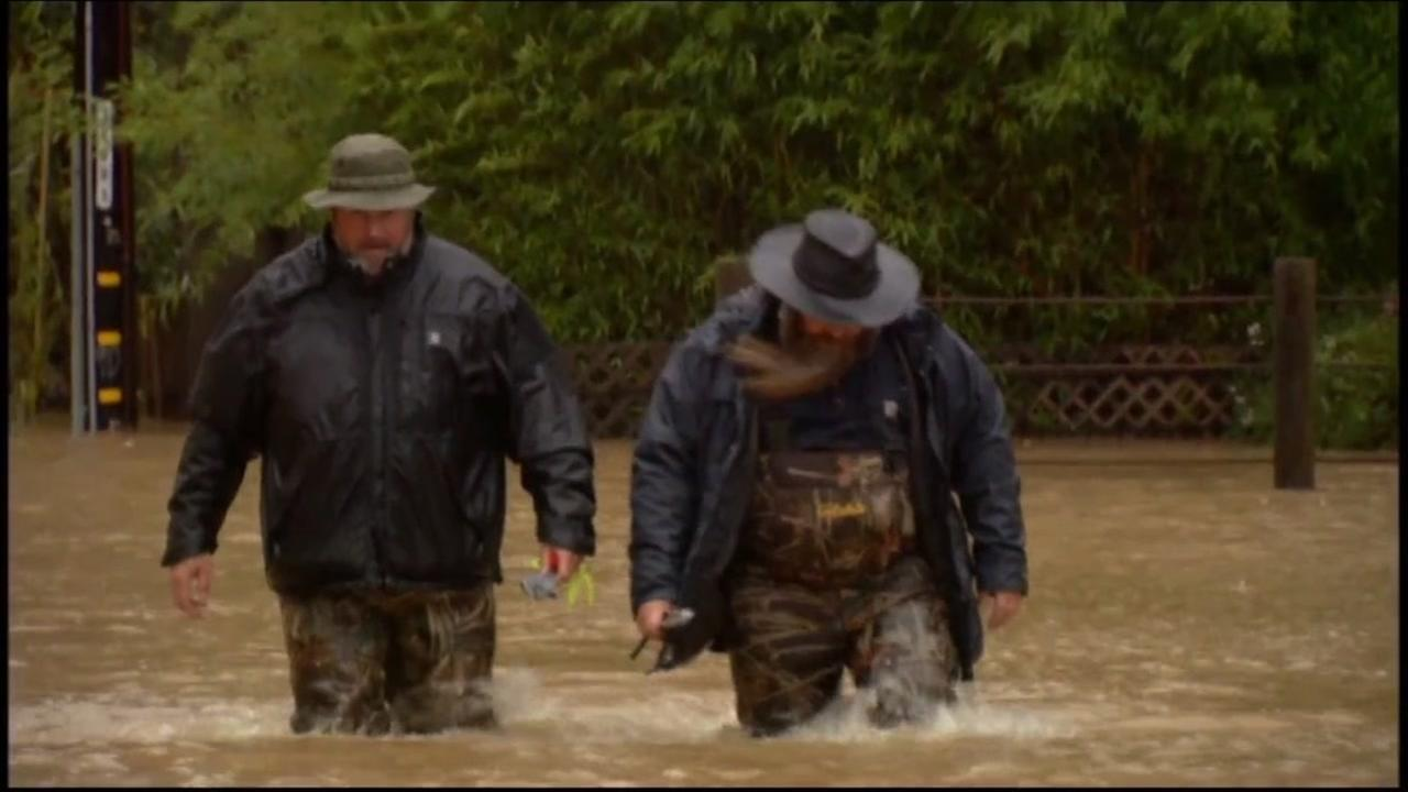 This is an undated image of two men walking in flood waters.