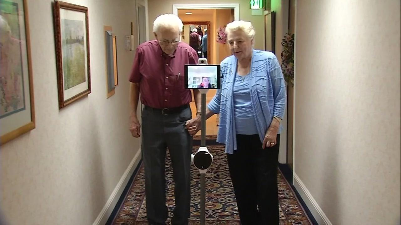 A couple walks down a hallway with their OhmniLabs robot in this undated image.