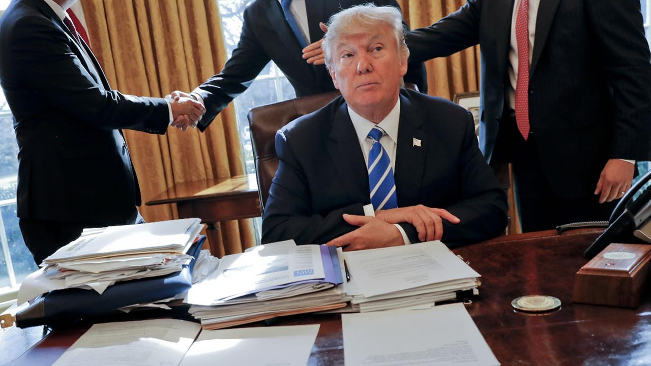 President Donald Trump sits at his desk after a meeting with Intel CEO Brian Krzanich, left, and members of his staff in the Oval Office Wednesday, Feb. 8, 2017 in Washington, D.C.