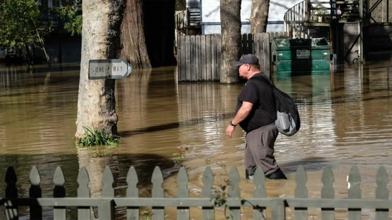 A man walks through deep floodwater in Guerneville, Calif. on Friday, Feb. 10, 2017.