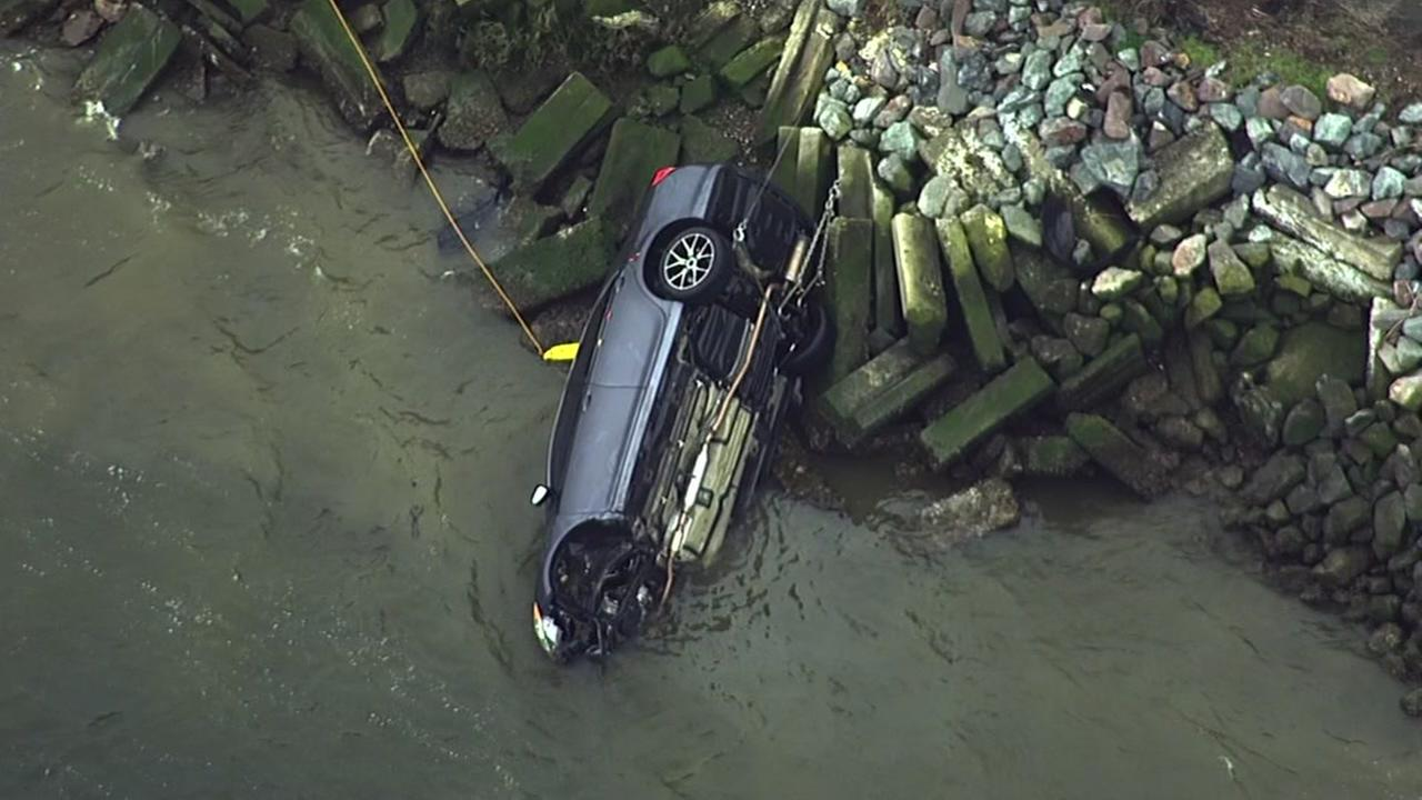 A car is seen being pulled from an estuary in Oakland, Calif. on Friday February 17, 2017.
