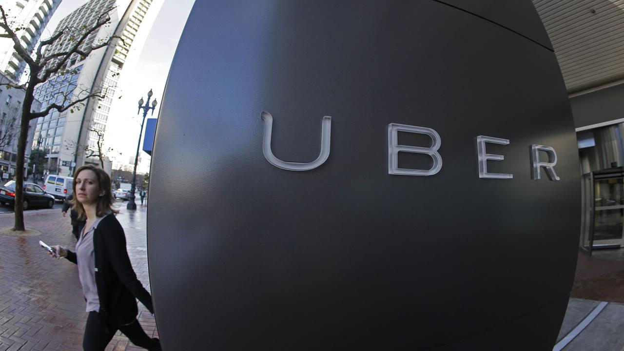 A woman walks past the company logo of the internet car service, Uber, in San Francisco on Dec. 16, 2014.