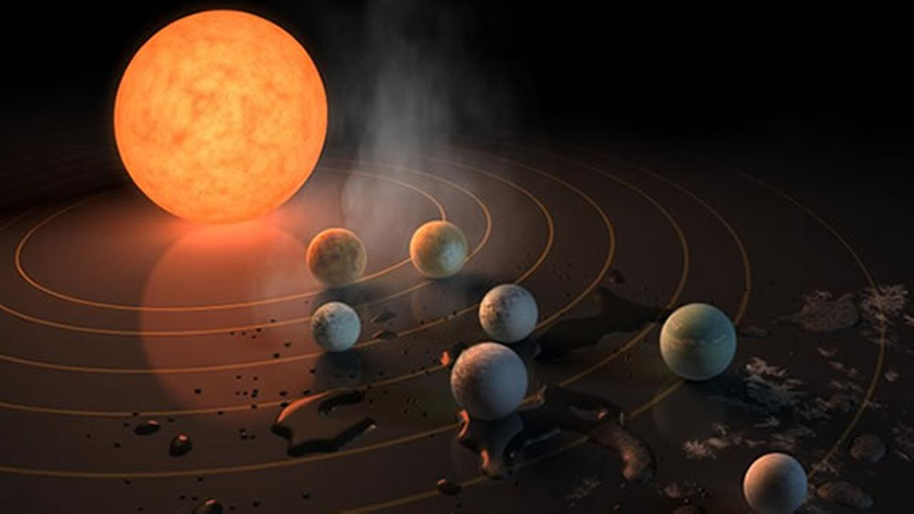 This illustration by NASA shows the TRAPPIST-1 star and seven Earth-sized planets orbiting it.