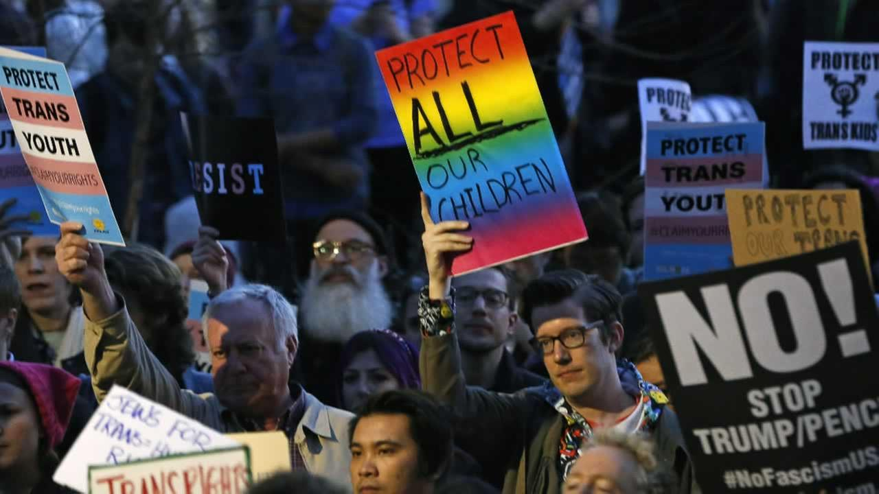 Protesters hold signs during a rally in support of transgender youth, Thursday, Feb. 23, 2017, at the Stonewall National Monument in New York.