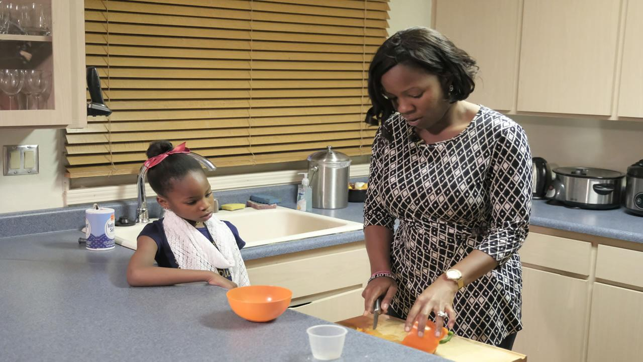 Dr. Nowando Olayiwola appears in her kitchen in Hercules, Calif. with one of her children on Feb. 23, 2017.