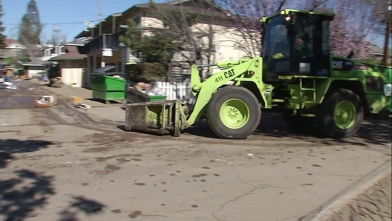 Volunteers moved debris while others power washed their homes in San Jose, Calif. on Sunday, Feb. 26, 2017.
