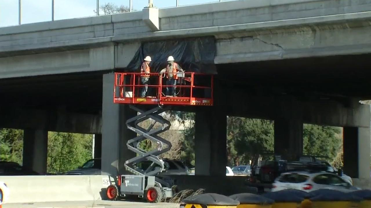 Caltrans workers are seen durveying a damaged overpass in Palo Alto, Calif. on Friday March 3, 2017.