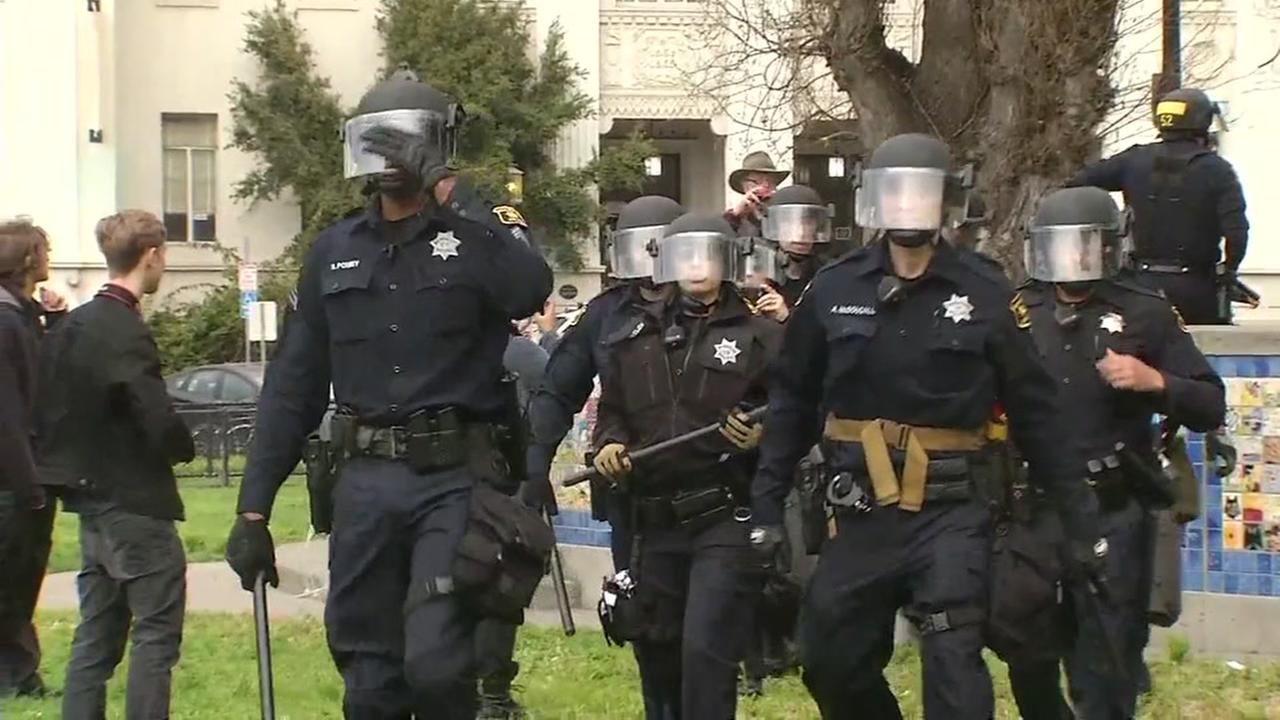 Police wearing riot gear walk through a protest in Berkeley, Calif. on Saturday, March 4, 2017.