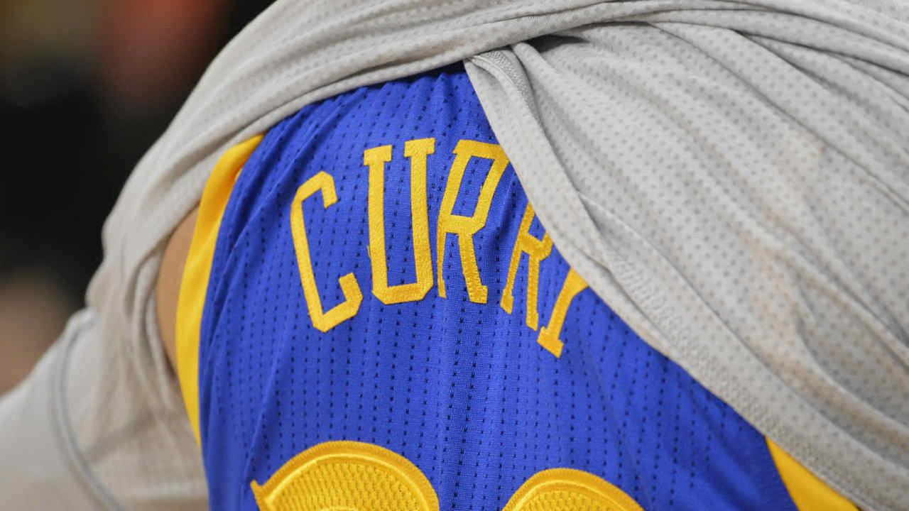 Golden State Warriors guard Stephen Curry removes his warm-up jersey before an NBA basketball game against the San Antonio Spurs.
