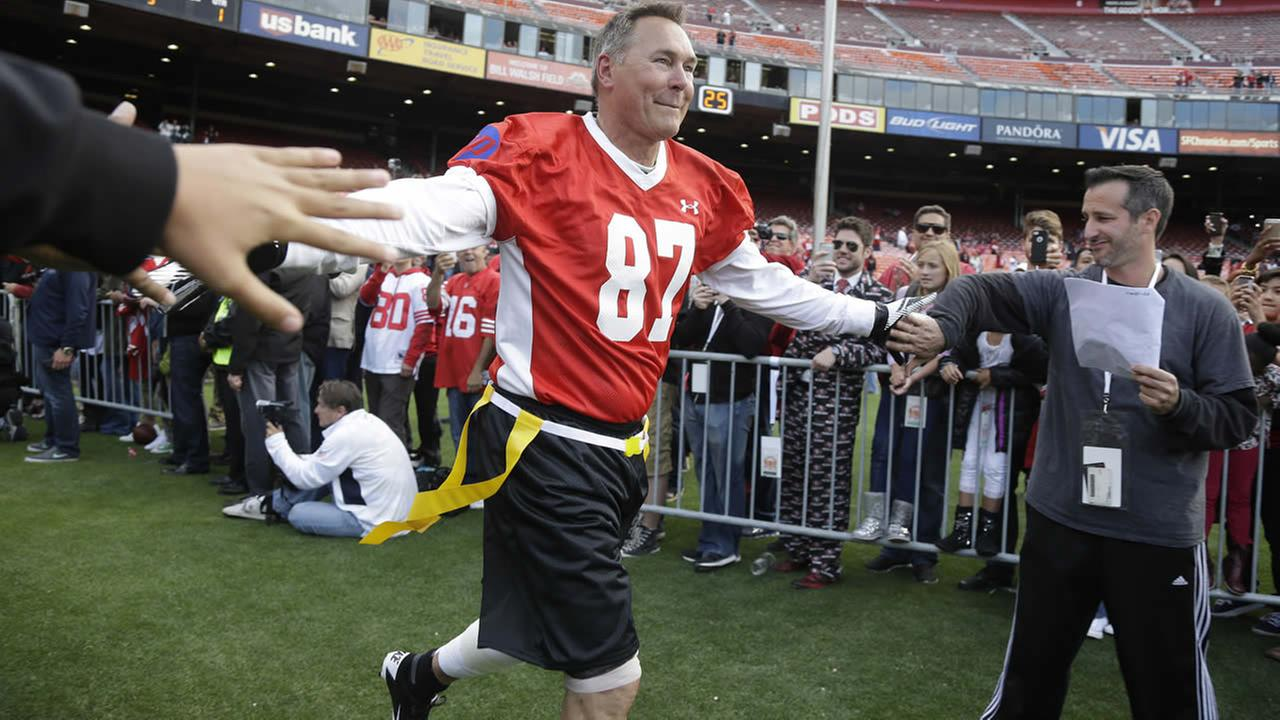 Former San Francisco 49ers Dwight Clark runs onto the field before the start of the Legends of Candlestick flag football game July 12, 2014, in San Francisco. (AP Photo)