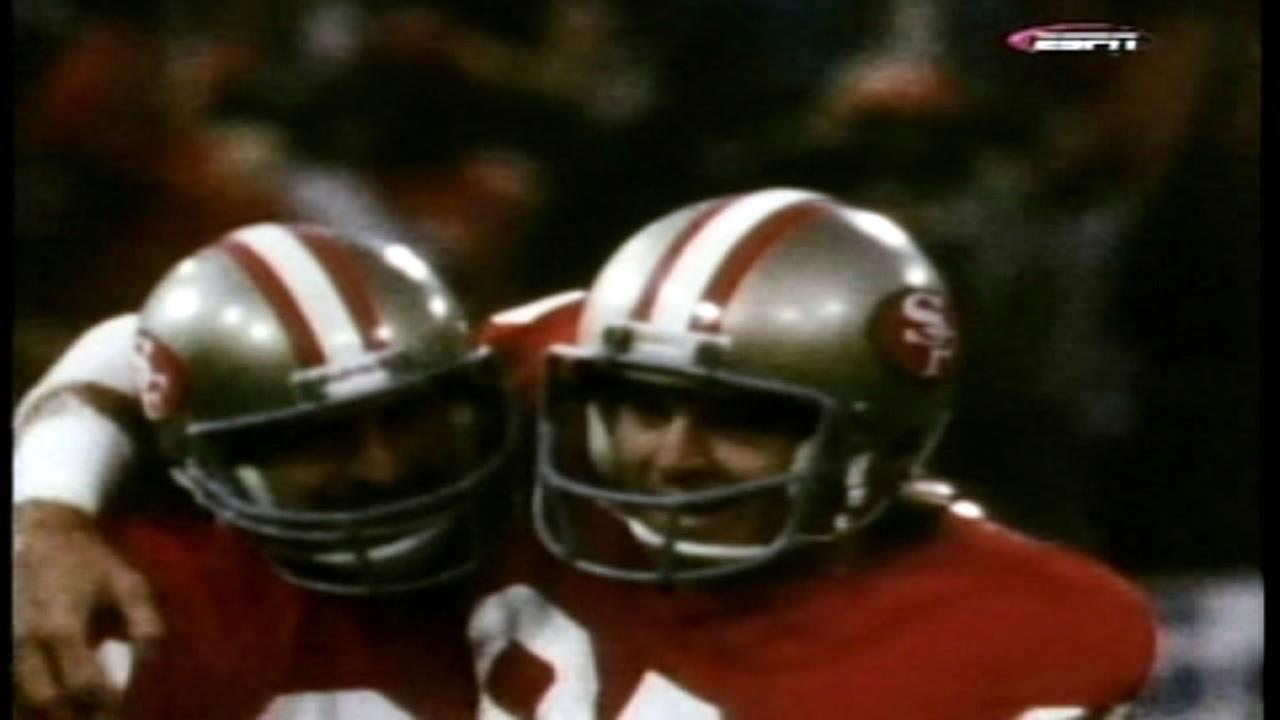 Mike Shumann hugs Dwight Clark during a San Francisco 49ers game.