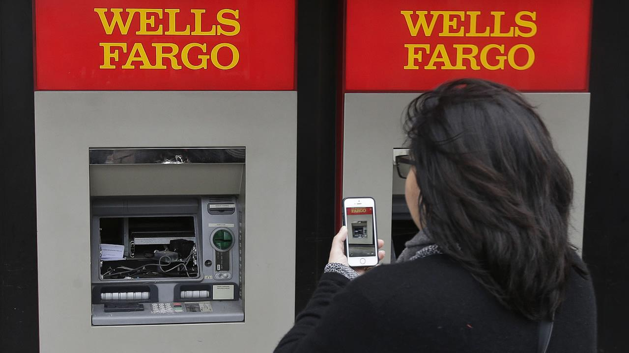 A woman takes a photo of damaged ATM machines at a Wells Fargo bank in Berkeley, Calif., Thursday, Feb. 2, 2017.