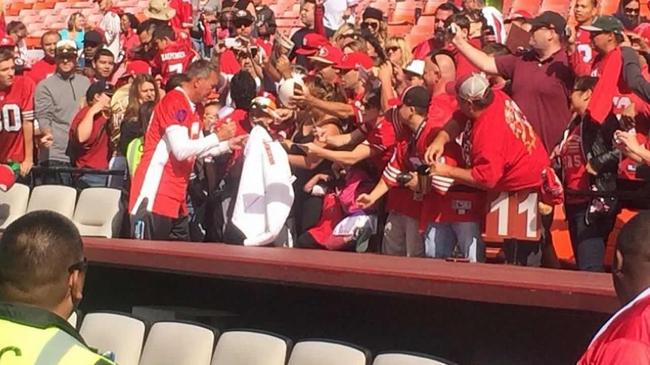 Dwight Clark is signing autographs ahead of the Legends Of Candlestick game.