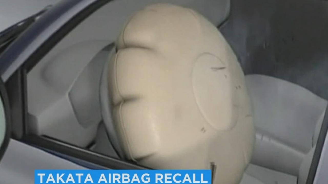 An air bag is shown expanded inside of a car.