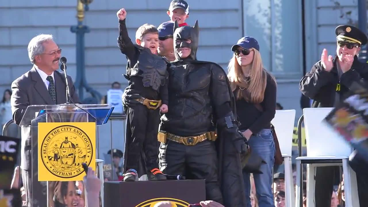 Batkid raises his fist at San Francisco City Hall.