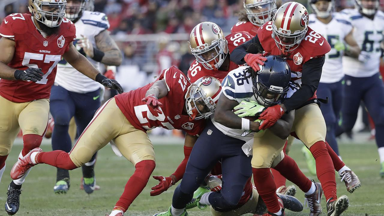 Seattle Seahawks running back Alex Collins, center, is tackled by 49ers defenders during the second half of an NFL football game in Santa Clara, Calif., Sunday, Jan. 1, 2017.