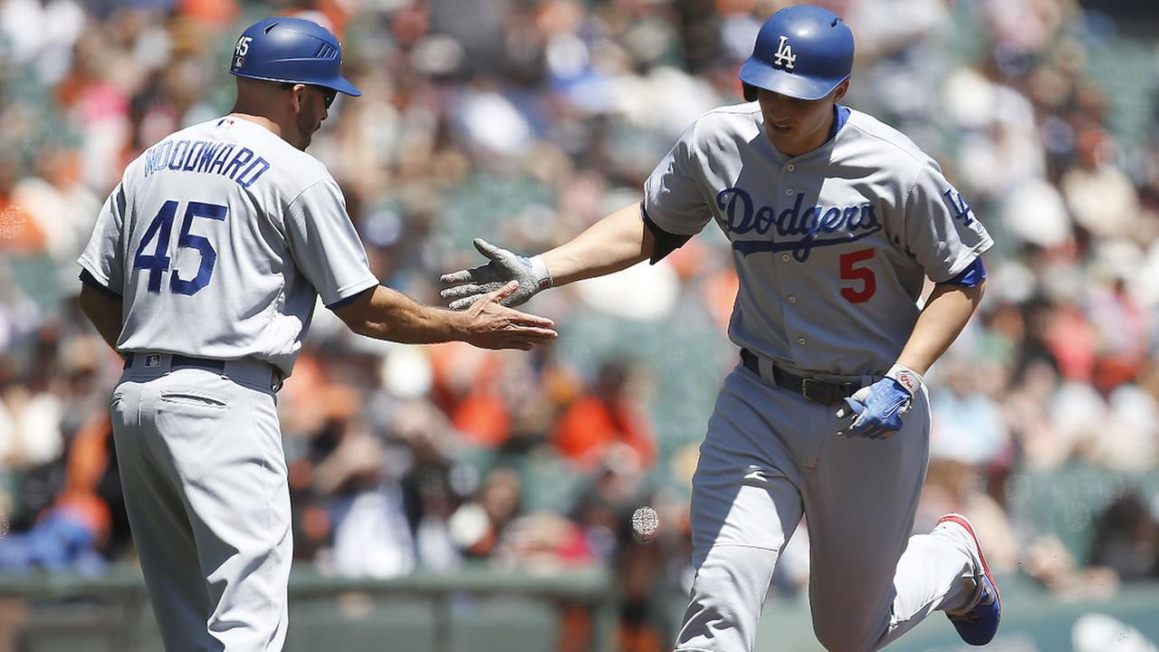 Dodgers Corey Seager is congratulated by third base coach Chris Woodward after hitting a solo home run against the Giants in San Francisco, Thursday, April 27, 2017.