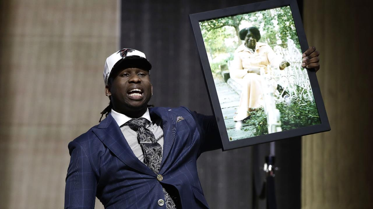 Takkarist McKinley carries a photograph of his grandmother after being selected by the Atlanta Falcons during the NFL football draft, Thursday, April 27, 2017, in Philadelphia.