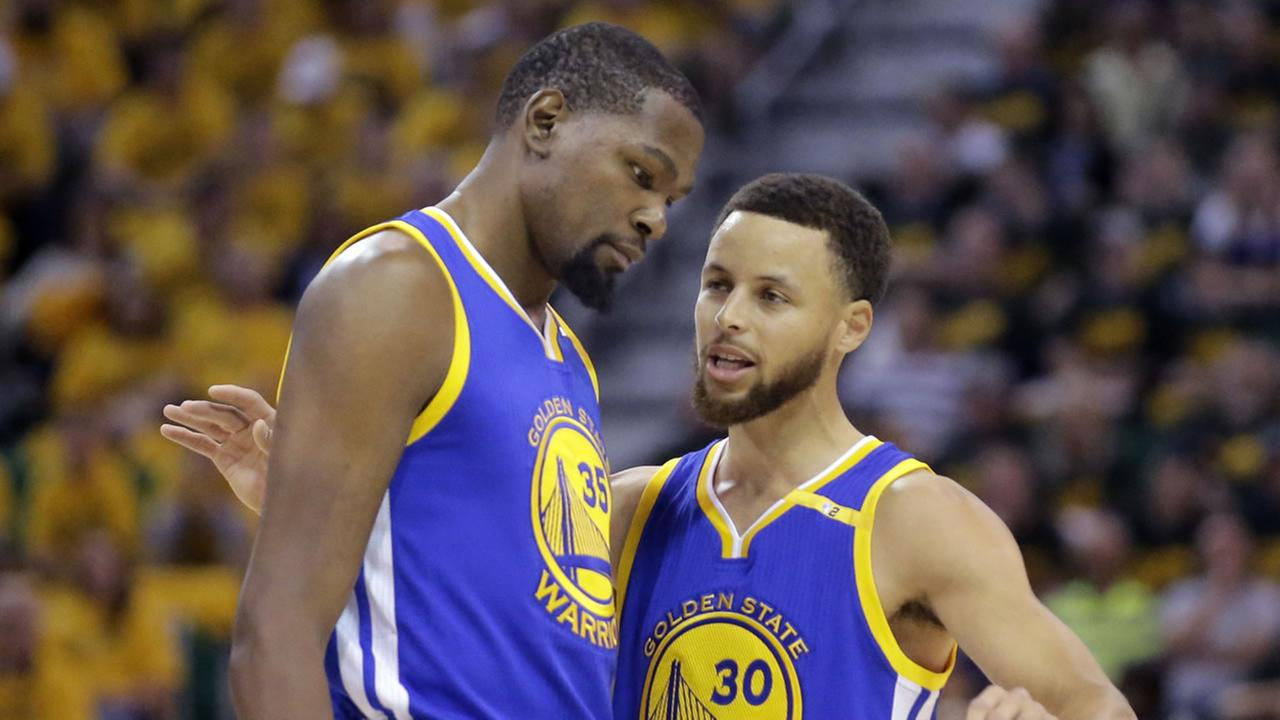 Golden State Warriors Stephen Curry and Kevin Durant talk in the first half during Game 3 of an NBA playoff series in Salt Lake City, Utah.