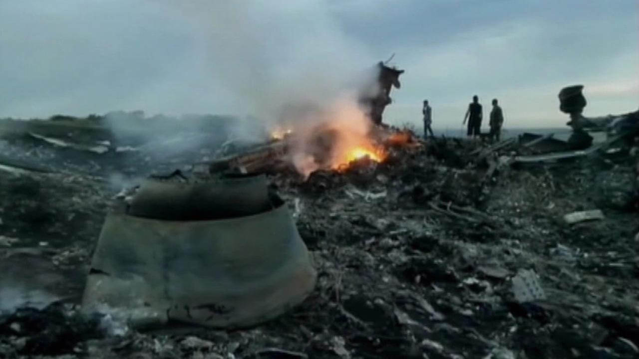 Investigators look at wreckage of Malaysia Airlines Flight 17 crash.