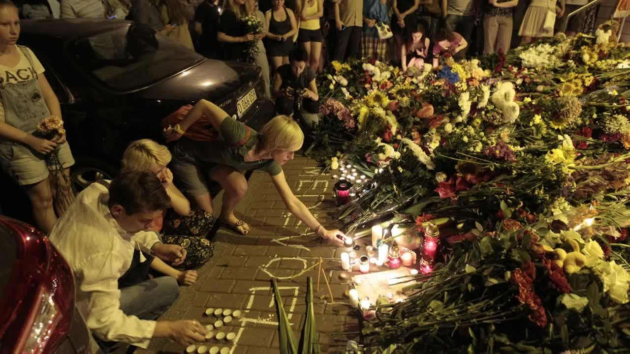 People hold candles and place flower tribute outside the Dutch embassy to commemorate victims of Malaysia Airlines plane crash in Kiev, Ukraine, Thursday, July 17, 2014.(AP Photo/Sergei Chuzavkov)