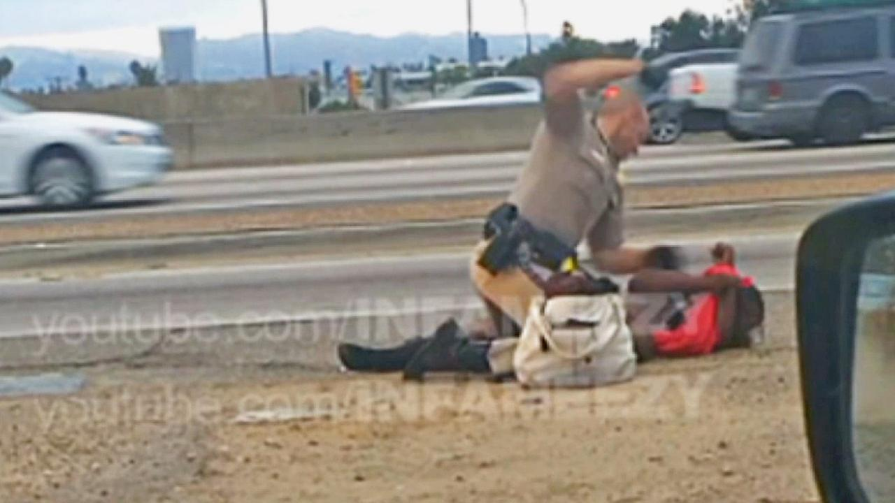 Still from video image shows woman being pummeled by a California Highway Patrol officer alongside a Los Angeles freeway.