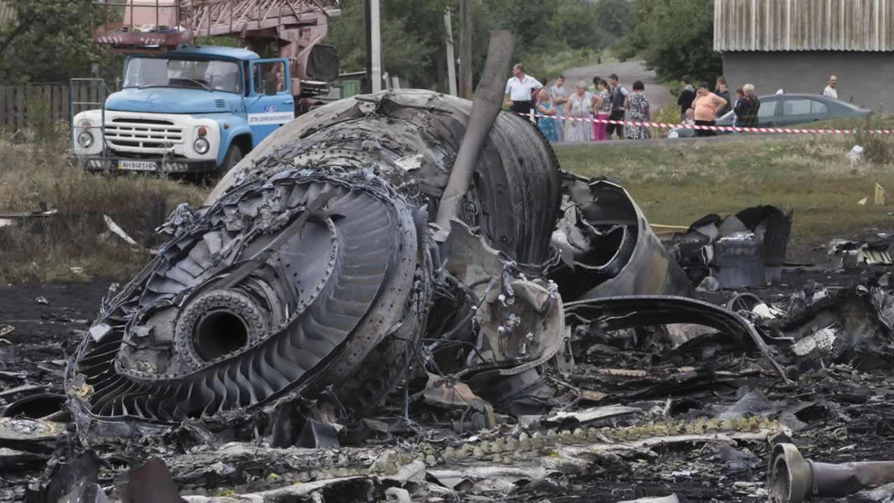 Local citizens, background, look at the site of a crashed Malaysia Airlines passenger plane near the village of Rozsypne, Ukraine, eastern Ukraine July 18, 2014. (AP Photo/Dmitry Lovetsky)AP Photo/Dmitry Lovetsky