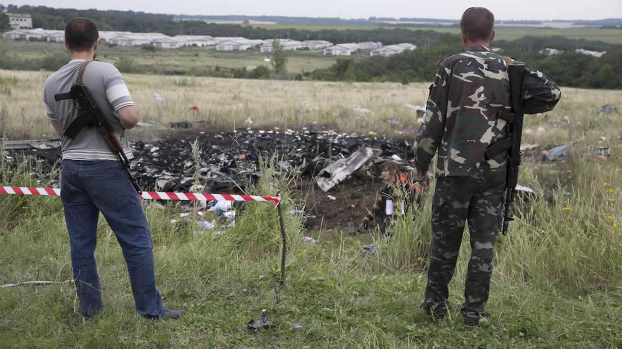 Pro-Russian fighters guard the site of a crashed Malaysia Airlines passenger plane near the village of Rozsypne, Ukraine, July 18, 2014. (AP Photo/Dmitry Lovetsky)