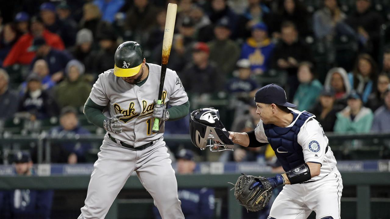 Seattle Mariners catcher Tuffy Gosewisch jumps up to chase a ball as Oakland Athletics Yonder Alonso looks on Monday, May 15, 2017, in Seattle.