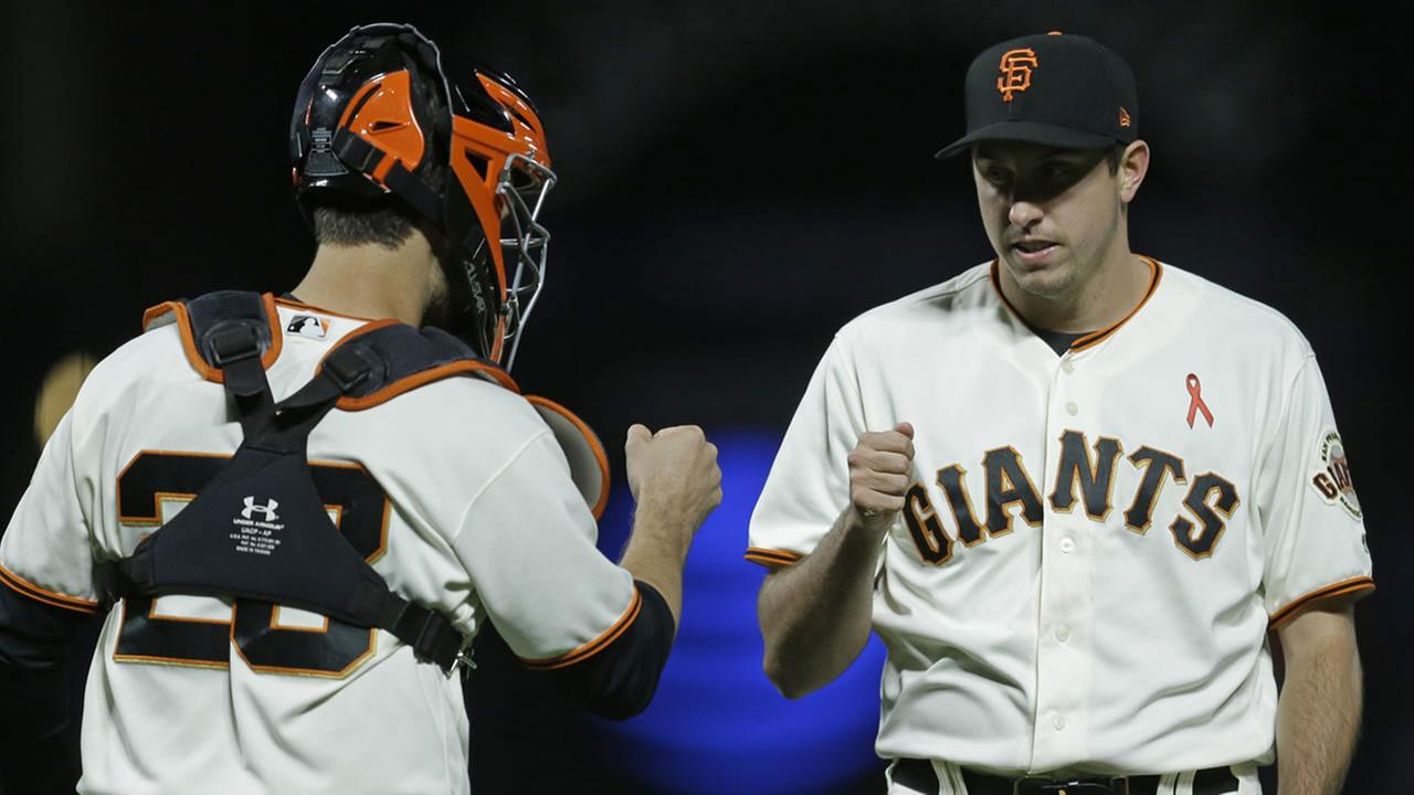 San Francisco Giants Derek Law and catcher Buster Posey celebrate the 8-4 win over the Los Angeles Dodgers at the end of a baseball game Monday, May 15, 2017, in San Francisco.