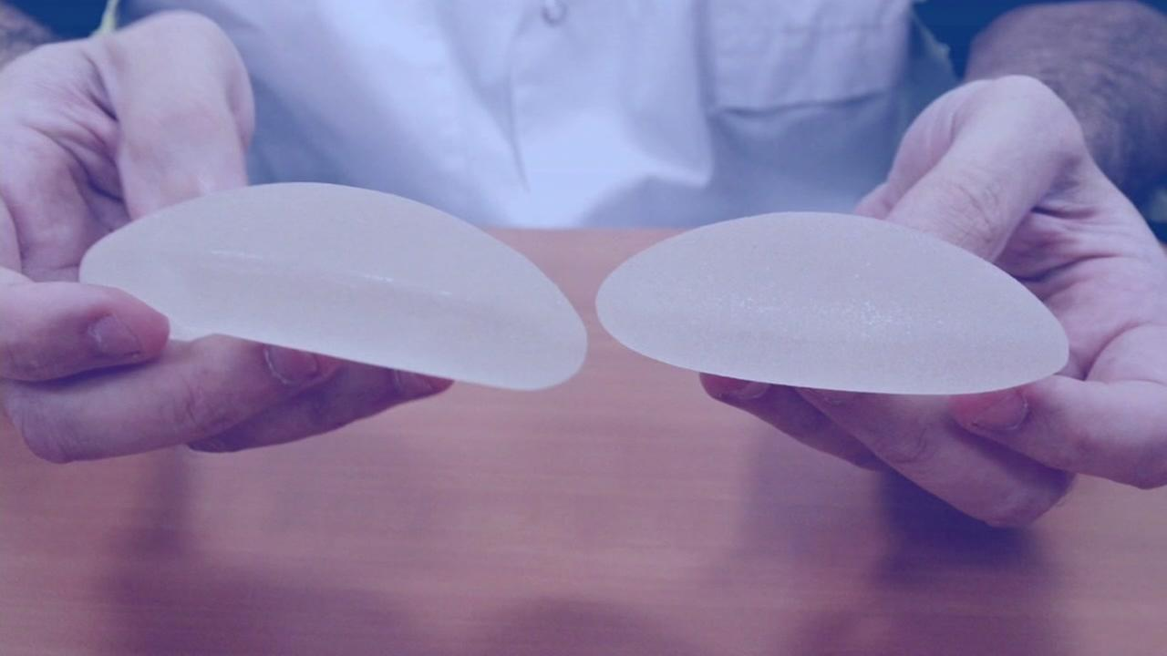 A plastic surgeon holds breast implants in this undated photo.