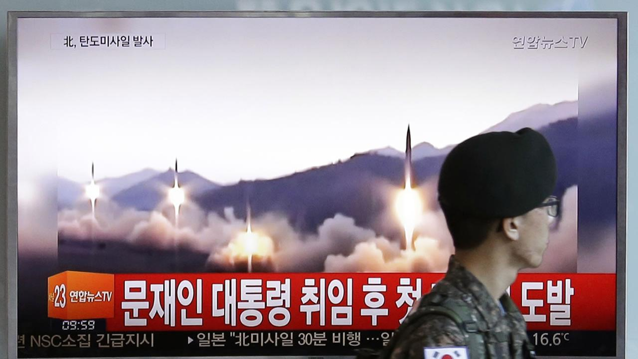 A South Korean army soldier walks by a TV news program showing a file image of missiles being test-launched by North Korea in Seoul, South Korea, May 14, 2017.