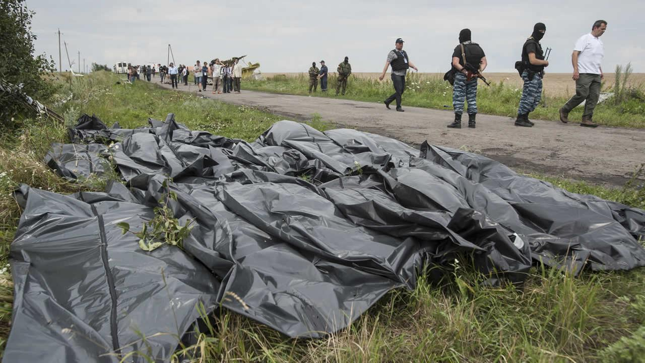 Pro-Russian fighters walk on a road with victims bodies lying in bags at crash site of a Malaysia jet in eastern Ukraine, Saturday, July 19, 2014 (AP Photo/Evgeniy Maloletka)