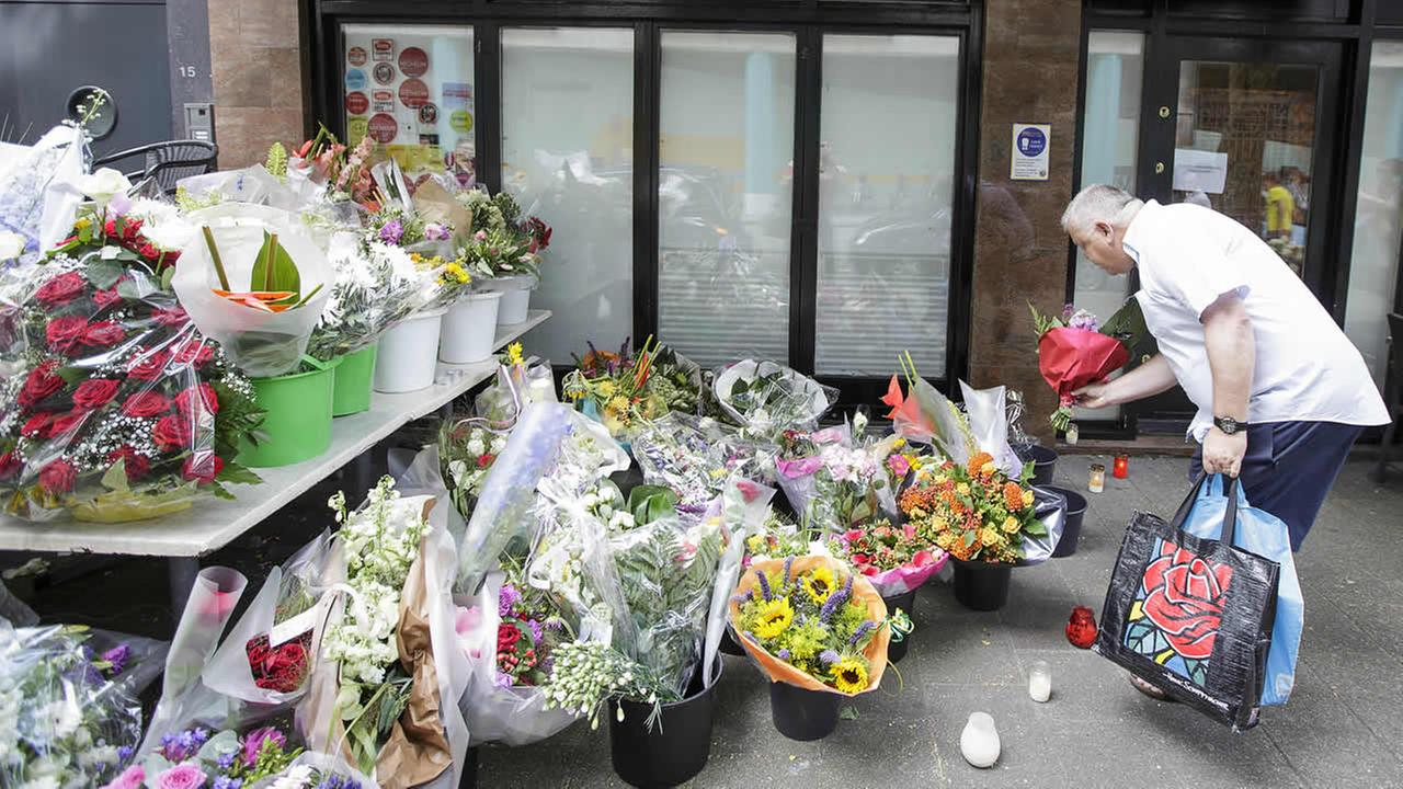 A man lays flowers in front of restaurant Asian Glories in Rotterdam, Saturday, July 19, 2014. (AP Photo/Phil Nijhuis)
