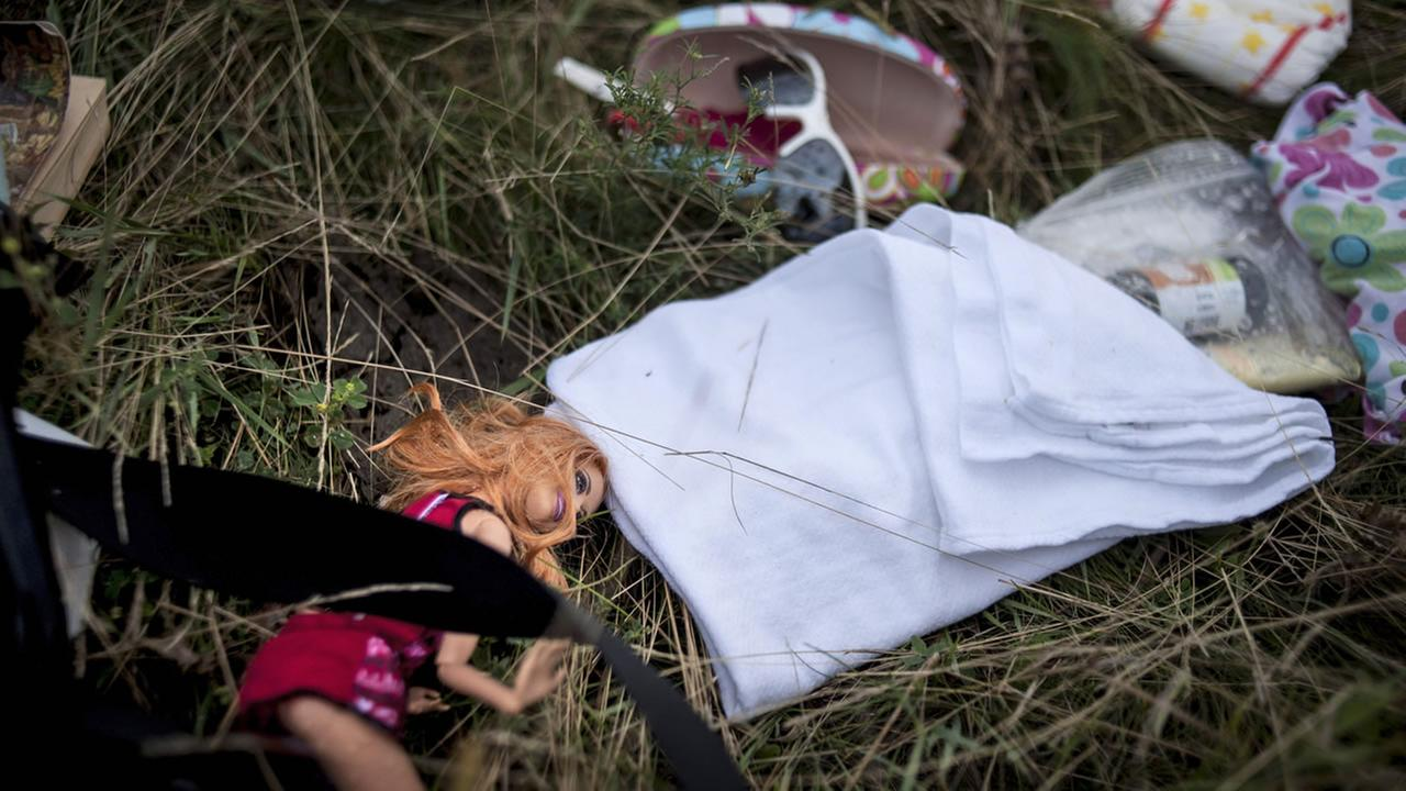 A doll and other personal effects lie on the ground at the crash site of a Malaysia Airlines jet in eastern Ukraine, Saturday, July 19, 2014.(AP Photo/Evgeniy Maloletka)