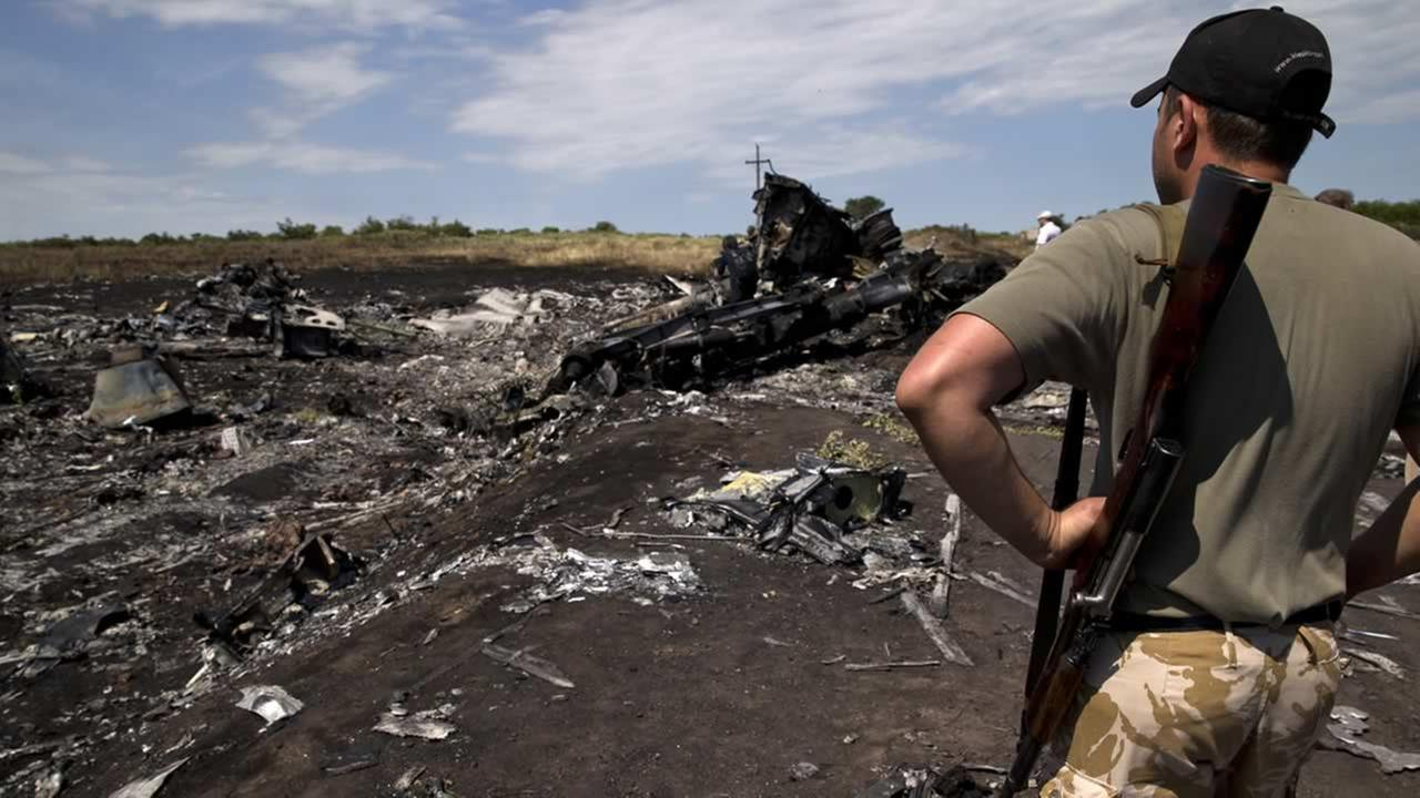 An armed man looks at charred debris at the crash site of Malaysia Airlines Flight 17 near the village of Hrabove, eastern Ukraine, Sunday, July 20, 2014. (AP Photo/Vadim Ghirda)