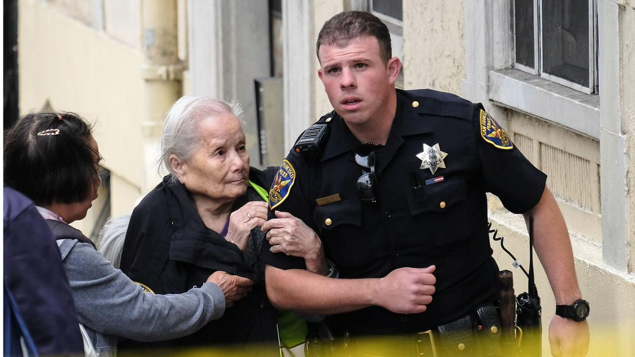 A San Francisco police officer evacuates an elderly woman from a building in the Tenderloin, San Francisco on Tuesday, May 30, 2017.