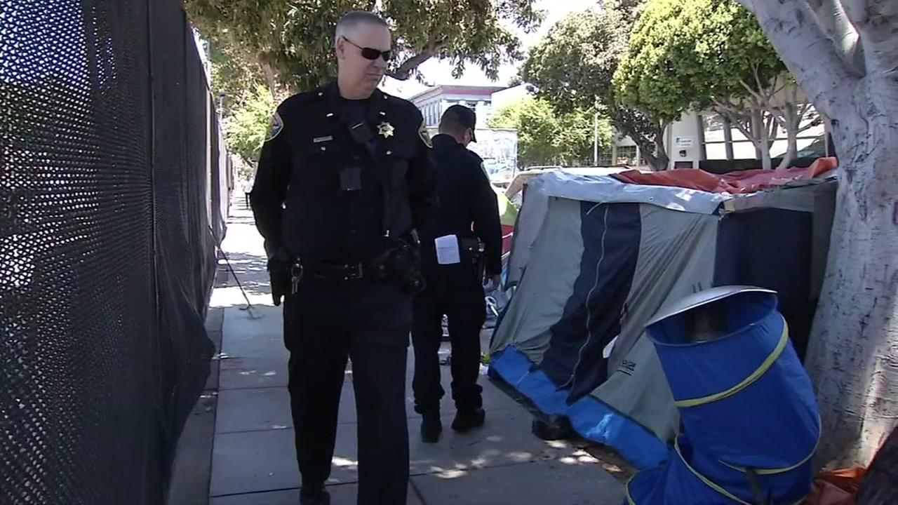 SFPD Officer Jared Harris and his partner, Officer Yasar Shah, speaks with tent dwellers in San Francisco on Wednesday, May 31, 2017.